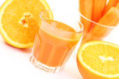 Carrot juice. Glass of carrot juice and some fresh carrots and orange royalty free stock photos
