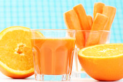 Carrot juice. Glass of carrot juice and some fresh carrots and orange Stock Photos