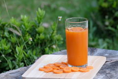 Carrot juice and carrot segments on a wooden background Stock Images
