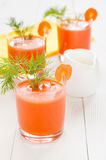 Carrot juice, decorated with sprig of dill. Carrot juice in glasses, decorated with a sprig of dill and a milk jug, on the background of yellow napkin and white Stock Images