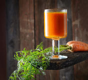 Carrot juice in a glass, carrots with tops on old blackboard on a wooden background Royalty Free Stock Images