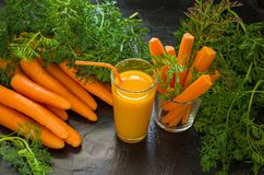 Carrot juice in a glass and ripe fresh carrots with green foliage on a dark stone background. Carrot juice in a glass Cup and raw carrot with leaves on a dark Stock Image