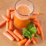 Carrot juice in a glass with small peeled carrots and mint Stock Photography
