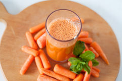 Carrot juice in a glass with small peeled carrots and mint Royalty Free Stock Image