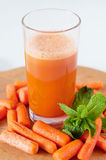 Carrot juice in a glass with small peeled carrots and mint Royalty Free Stock Photography