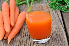 Carrot juice in a glass on wooden table Stock Photos