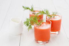 Carrot juice in glasses. Decorated with a sprig of dill and a milk jug, on the background of white boards Royalty Free Stock Photos