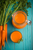 Carrot juice. Homemade natural carrot juice in glass on rustic blue wooden table in background Royalty Free Stock Photos