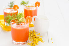 Carrot juice, milk jug and mimosa branch. Carrot juice in three glasses, decorated with dill, milk jug and mimosa branch on the background of yellow napkin and Royalty Free Stock Photos