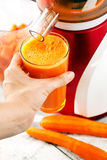 Carrot juice. Slow juicer and carrot juice. Juicing process Royalty Free Stock Photography