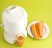 Carrot juice and squeezer. Glass with vegetable juice juicer carrot on plate Royalty Free Stock Photography