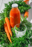 Carrot juice still life. A bottle of carrot juice with empty glass and some fresh carrots on white wood table. Still life of a healthy eating concept Stock Photography