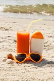 Carrot juice, sunglasses and sun lotion at beach, concept of vitamin A and beautiful, lasting tan. Carrot juice, sunglasses and sun lotion on sand at beach royalty free stock photo