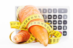 Carrot with a measure tape wrapped around and calculator isolated on a white background Royalty Free Stock Images