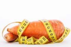 Carrot with a measure tape wrapped around  on a white Royalty Free Stock Images
