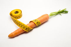 Carrot with measuring tape around it Stock Images