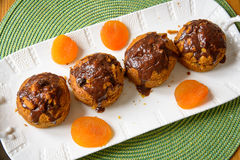 Carrot muffins with dried apricots. On a white plate with chocolate Stock Photography