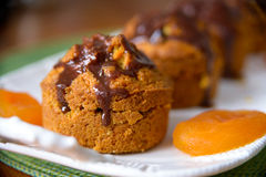 Carrot muffins with dried apricots. On a white plate with chocolate Royalty Free Stock Photo