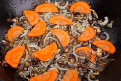 Carrot and onion are being boiled in pan Stock Image