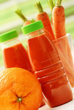 Carrot and orange juice. Bottle of carrot and orange juice with fresh fruits - food and drink Royalty Free Stock Photography