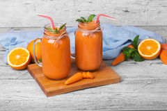 Carrot and orange juice. Bottles of healthy, organic, fruit smoothie on a wooden background. Vegan cocktail. Copy space. royalty free stock photo