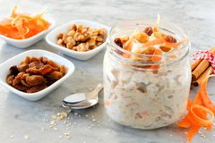 Carrot overnight oats with nuts and raisins in a mason jar on marble. Carrot cake overnight oats with nuts and raisins in a mason jar, still life on marble Stock Image
