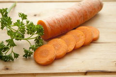 Carrot with parsley. On edge board Royalty Free Stock Images