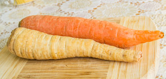 Carrot and parsnip on a wooden plate and decorated cover Royalty Free Stock Images