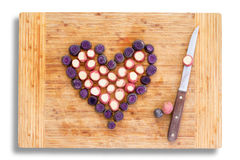 Carrot pieces in the shape of a heart with knife. Purple carrots chopped into pieces in the shape of a heart with knife. Radishes in the middle for pink color Royalty Free Stock Image
