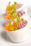 Carrot and radish salad. In white bowls royalty free stock photo