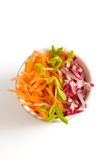 Carrot and radish salad with p. Carrot and radish salad in white bowl on white background stock photo