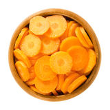 Carrot slices in wooden bowl over white Stock Images