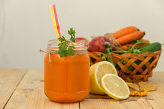 Carrot smoothie in a glass jar and vegetables. Stock Photos