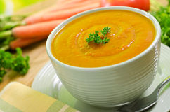 Carrot Soup. A delicious bowl of creamy hot carrot soup with field carrots and tomato background Royalty Free Stock Images