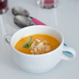 Carrot soup. With almonds in a white bowl and with colorful spoons Royalty Free Stock Image