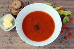 Carrot soup, with crackers and butter. Arrot soup in a white bowl, with crackers and butter Royalty Free Stock Image