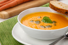 Carrot Soup. Creamy carrot soup with basil oil, garnished with herb whole wheat bread. Fresh carrots around Royalty Free Stock Images