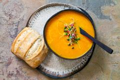 Carrot soup with green sprouts. Carrot soup with the topping of green sprouts stock photo