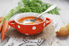 Carrot soup. In orange bowl on the table Stock Photo
