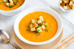 Carrot Soup. Vegetable Carrot Soup with Croutons, Greens and Spices in white bowl - healthy fresh homemade vegan vegetarian diet organic meal food lunch soup Royalty Free Stock Photo