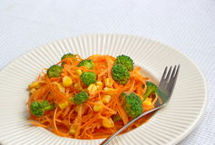 Carrot spaghetti with fresh vegetable served on white tablecloth Stock Photography