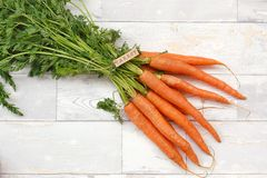 Carrot with tha label on the wooden background stock photography