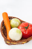 Carrot, tomato and onions in the basket Stock Photos