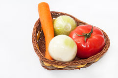 Carrot, tomato and onions in the basket Royalty Free Stock Photography