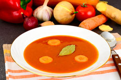 Carrot Tomato Soup in Plate. Behind lie on the soup ingredients, Stock Images