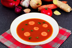 Carrot Tomato Soup in Plate. Behind lie on the soup ingredients, Stock Image