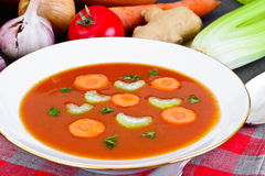 Carrot Tomato Soup in Plate. Behind lie on the soup ingredients, Stock Photos