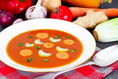 Carrot Tomato Soup in Plate. Behind lie on the soup ingredients, Royalty Free Stock Photo