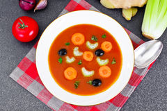 Carrot Tomato Soup in Plate. Behind lie on the soup ingredients, Stock Photo