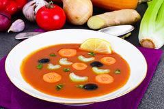 Carrot Tomato Soup in Plate. Behind lie on the soup ingredients, Stock Photography